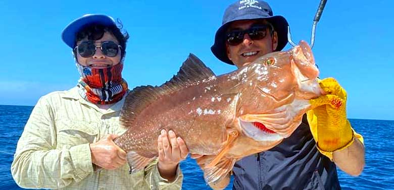 Two Friends Holding Fish | FishyBizness Fishing Charters & Boat Tours in Naples, Florida